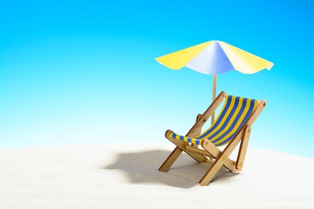 Een chaise longue onder een parasol op het zandstrand met kopieerruimte