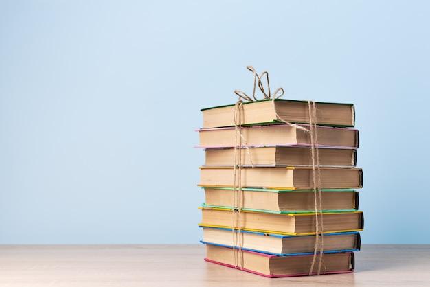 Een chaotische stapel boeken vastgebonden met een touw staat op een houten tafel tegen een lichtblauwe muur