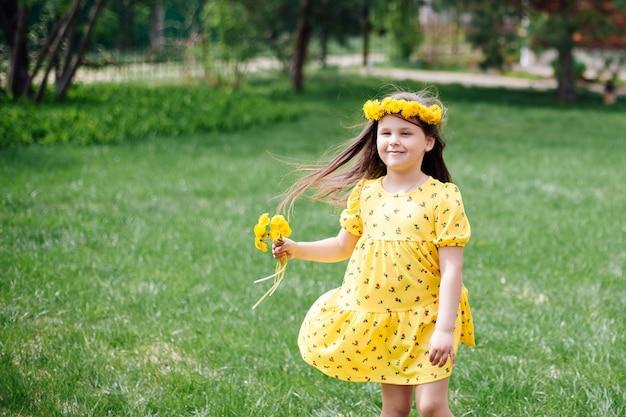 Een charmant gelukkig meisje in een jurk die in de wind vliegt, rent op het groene gras en met paardebloemen in h...