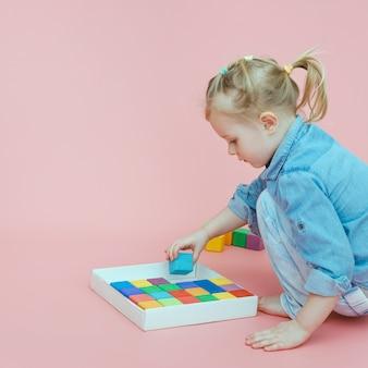 Een charmant klein meisje in denimkleren op een roze achtergrond