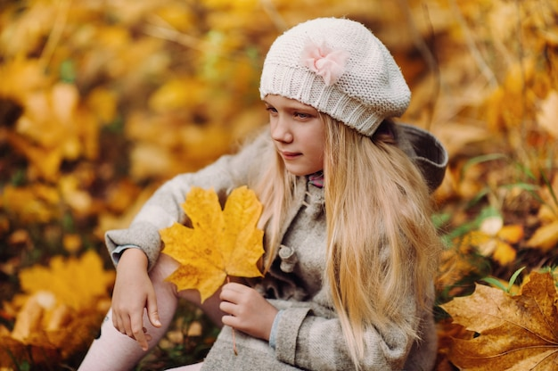 Een charmant klein meisje in een jas zit in de herfst met een blad in haar handen.