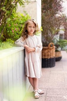 Een charmant klein meisje in een retro jurk en een grote strik op haar hoofd loopt op een zonnige zomerdag door de stad. gelukkige kinderen lachen op straat.