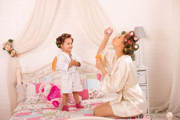 Een charmant klein meisje met haar moeder in haarkrulspelden speelt met zeepballen.
