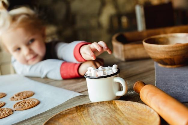 Een charmant klein meisje reikt naar marshmallows in een kopje cacao, dat op een tafel staat