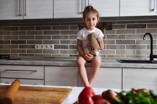 Een charmant klein meisje zit op een aanrecht in de keuken met een zacht pluche speelgoed in haar handen. groenten op de tafel op de voorgrond