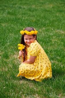 Een charmant lachend meisje in een gele jurk zit gehurkt op het gazon met een krans en een boeket van je...