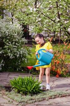 Een charmant lachend meisje in volle groei water bloeit uit een gieter buiten een mooie blo...