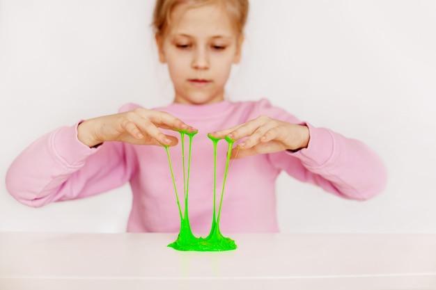 Een charmant meisje heeft een handgemaakt speelgoed genaamd slijm