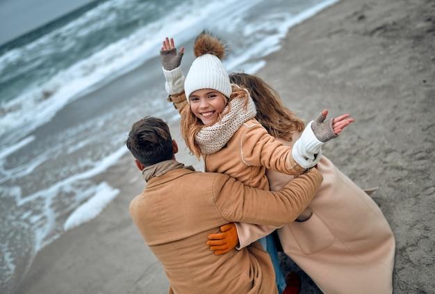 Een charmant meisje in een gebreide muts en wanten met haar ouders ontspant in de winter aan de kust.
