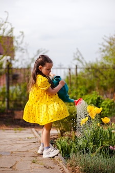 Een charmant meisje in een gele jurk wappert in de wind en geeft gele tulpen water uit een gieter in...