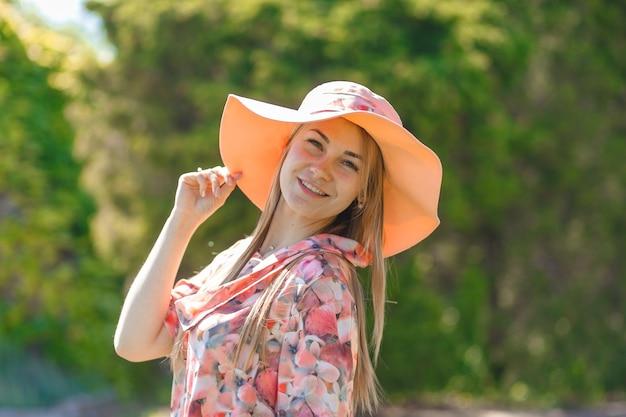 Een charmant meisje in een lichte zomerjurk en een pareo-hoed loopt in een groen park.