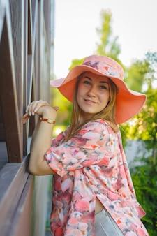 Een charmant meisje in een lichte zomerjurk en een pareohoed loopt in een groen park. geniet van warme zonnige zomerdagen.