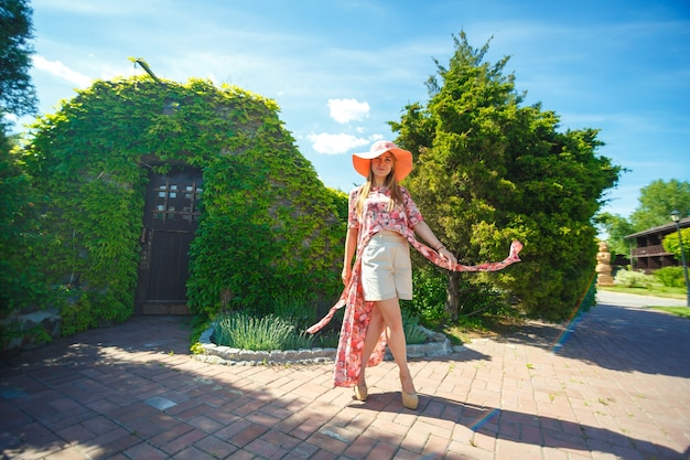 Een charmant meisje in een lichte zomerjurk en een pareohoed loopt in een groen park