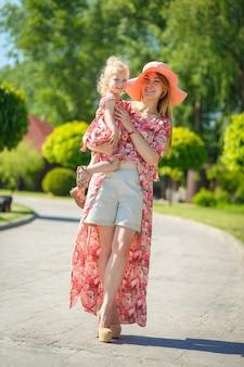 Een charmant meisje in een lichte zomerjurk loopt in een groen park met haar dochtertje en houdt haar in haar armen.