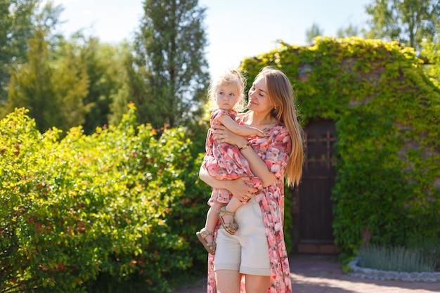 Een charmant meisje in een lichte zomerjurk loopt met haar dochtertje in een groen park en houdt haar in haar armen. geniet van warme zonnige zomerdagen.