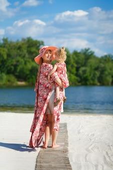 Een charmant meisje in een lichte zomerjurk loopt met haar dochtertje op het zandstrand.