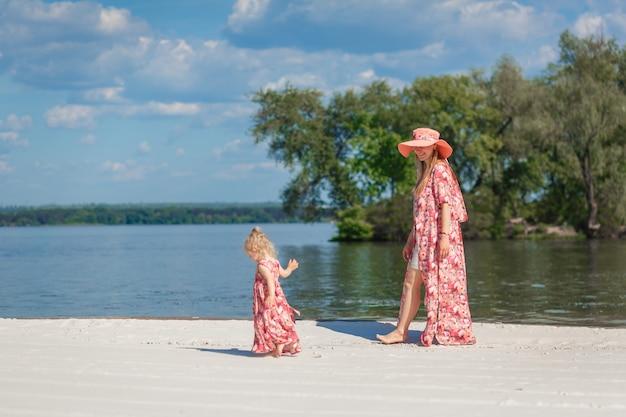 Een charmant meisje in een lichte zomerjurk loopt met haar dochtertje over het zandstrand. geniet van warme zonnige zomerdagen.