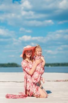 Een charmant meisje in een lichte zomerjurk loopt met haar dochtertje over het zandstrand.