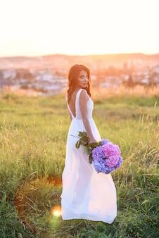 Een charmant meisje in een witte jurk met een boeket van tedere gekleurde bloemen loopt in het gazon bij zonsondergang.