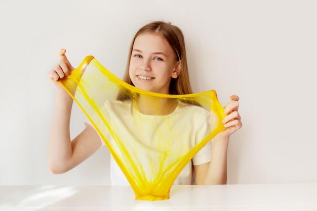 Een charmant meisje lacht en speelt met geel slijm