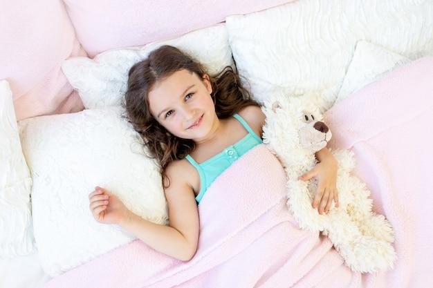 Een charmant meisje van 5-6 jaar oud knuffelt een teddybeer.