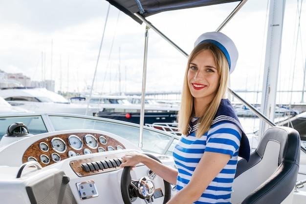 Een charmante blondine met lang haar in een jurk in zee-stijl zit van jachten en de zee het concept van recreatie en zeereizen