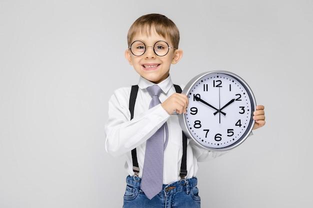 Een charmante jongen in een wit overhemd, bretels, een stropdas en een lichte jeans staat op een grijze muur.