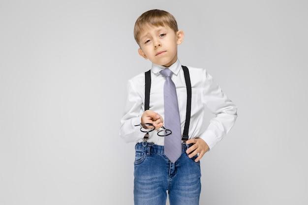 Een charmante jongen in een wit shirt, jarretels, een stropdas en een lichte spijkerbroek staat