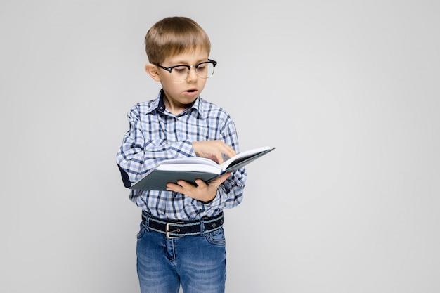 Een charmante jongen met een ingelegd shirt en een lichte jeans staat op een grijze. de jongen houdt een boek in zijn handen. jongen met een bril