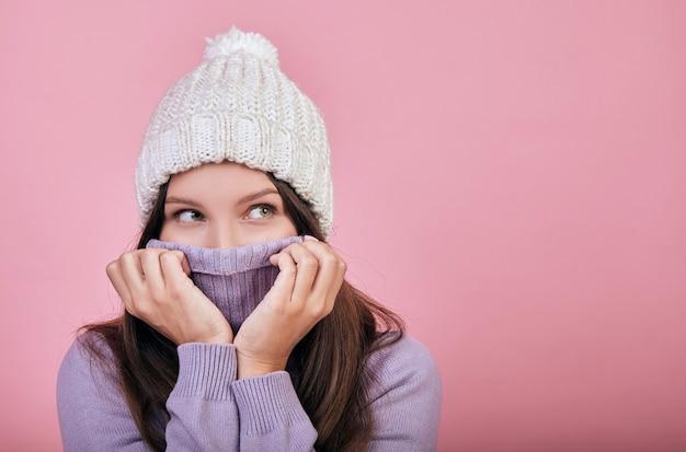 Een charmante schattige vrouw met donker golvend haar onder een sneeuwwitte hoed kijkt zijwaarts.