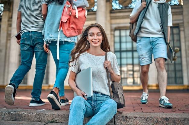 Een charmante studente met een rugzak en een laptop zit op de trap bij de campus tegen de achtergrond van passerende studenten.