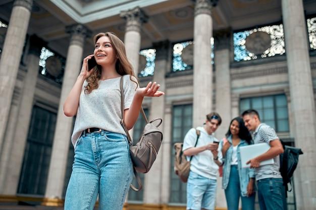 Een charmante studente met een rugzak praat op een smartphone tegen de achtergrond van een groep studenten in de buurt van de campus.
