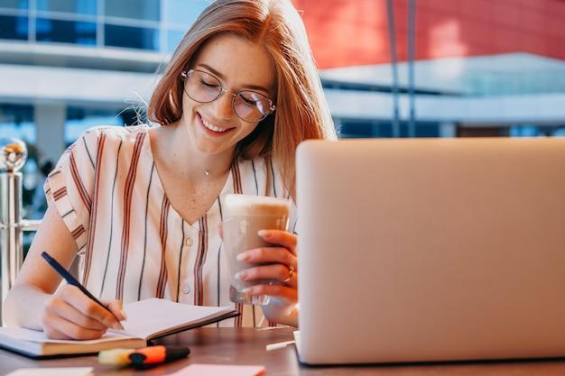 Een charmante zakenvrouw ziet er druk uit terwijl ze taken schrijft voor haar werknemers