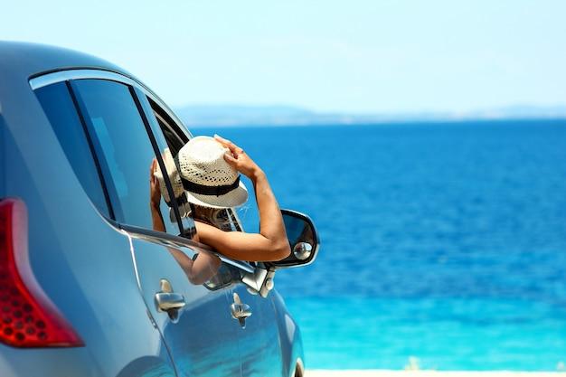 Een chauffeursmeisje in auto op zee in de zomer