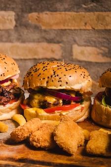 Een cheeseburger met groenten in het midden van twee andere hamburgers
