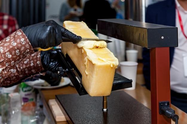 Een chef-kok bereidt een gerecht met raclette met behulp van een speciaal instrument voor het smelten van kaas.