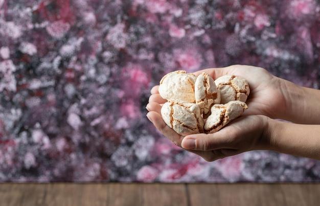 Een chef-kok die boterkoekjes bij de hand houdt.