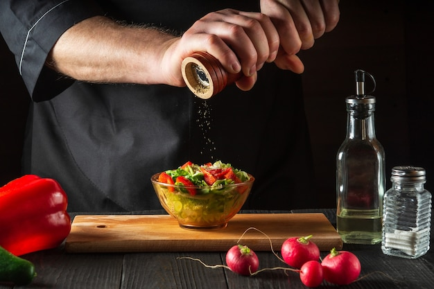 Een chef-kok in een restaurantkeuken voegt paprika's toe aan een verse groentesalade