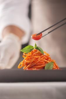 Een chef-kok in een wit uniform en handschoenen serveert cherrytomaatjes in pasta in tomatensaus met basilicumblaadjes met een pincet. haute cuisine. voedsel plateren