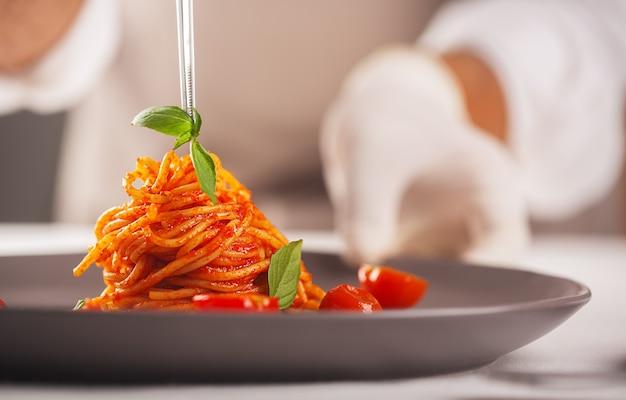 Een chef-kok in handschoenen en een wit uniform gebruikt een pincet om een gastronomisch gerecht van pasta in tomatensaus met kerstomaatjes te versieren, voedsel te plateren