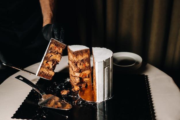 Een chef-kok met zwarte handschoenen snijdt een chocoladebruidstaart