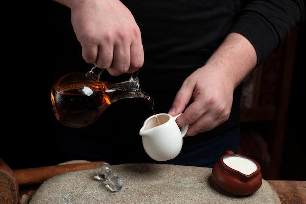 Een chef-kok olie uit glazen fles in de keramische pot