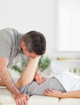 Een chiropractor strekt het been van de vrouw uit