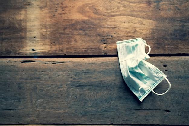 Een chirurgisch masker ter voorkoming van coronavirus wordt gebruikt en vervolgens op een houten tafel geplaatst.
