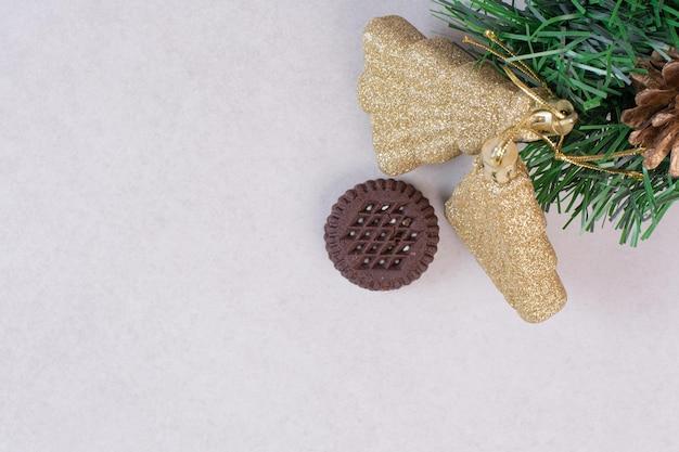 Een chocoladekoekje met kerstspeelgoed op witte tafel.