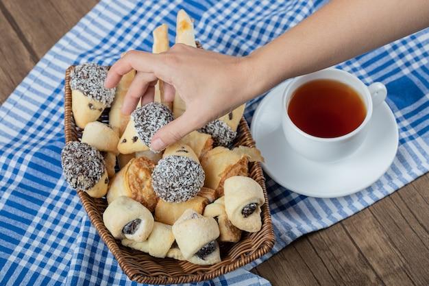 Een chocoladekoekje uit een houten dienblad halen met een kopje thee eromheen.