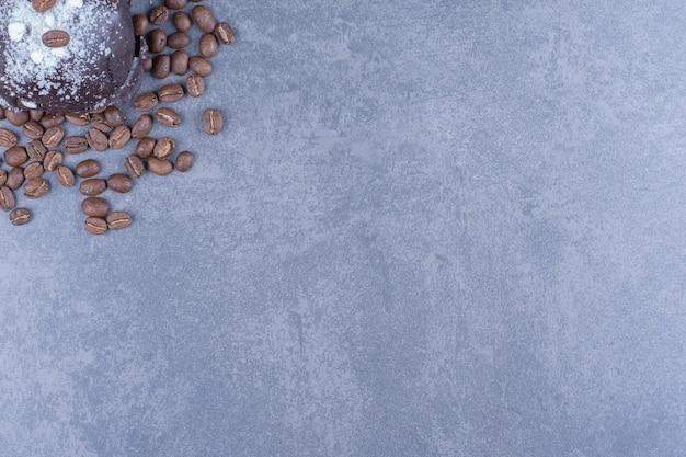 Een chocolademuffin met koffiebonen en suikerpoeder