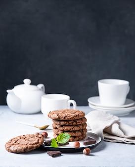 Een chocoladeschilferkoekjes met noten en munt met kop thee en theepot op een lichte lijst. vooraanzicht en kopieerruimte