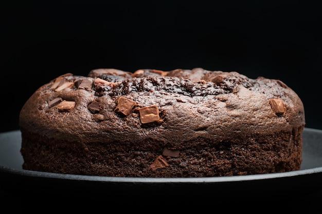 Een chocoladetaart op een grijze plaat op een donkere achtergrond