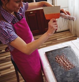 Een chocolatier die een cakeschraper gebruikt om overtollige chocolade uit mallen te verwijderen in een marmeren oppervlak om snoepschalen te maken. productie van zelfgemaakte luxe pralines en truffels